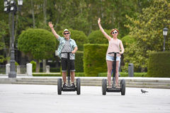 Young happy tourist couple riding segway enjoying city tour in Madrid park in Spain together Royalty Free Stock Images