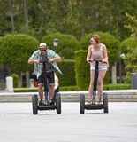 Young happy tourist couple riding segway enjoying city tour in Madrid park in Spain together Stock Image