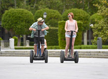 Young happy tourist couple riding segway enjoying city tour in Madrid park in Spain together Stock Photos