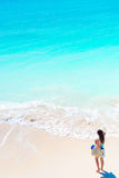Young happy tourist girl at beach in shallow water. Top view of a young girl and a snow-white beach with turquoise clean stock photography