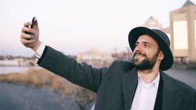 Young happy tourist man in ahat and coat smiling while taking selfie picture with mobile phone on city riverside royalty free stock photography