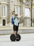 Young happy tourist man with backpack riding city tour segway driving happy and excited visiting Madrid palace Royalty Free Stock Images