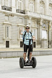 Young happy tourist man with backpack riding city tour segway driving happy and excited visiting Madrid palace Stock Photos
