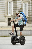 Young happy tourist man with backpack riding city tour segway driving happy and excited visiting Madrid palace Royalty Free Stock Photo
