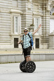 Young happy tourist man with backpack riding city tour segway driving happy and excited visiting Madrid palace Stock Photography