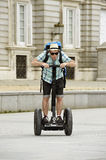 Young happy tourist man with backpack riding city tour segway driving happy and excited visiting Madrid palace Royalty Free Stock Photos