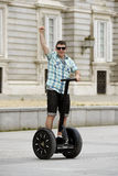 Young happy tourist man riding city tour segway driving happy and excited visiting Madrid palace Stock Photo