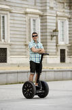 Young happy tourist man riding city tour segway driving happy and excited visiting Madrid palace Royalty Free Stock Image