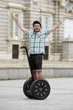 Young happy tourist man wearing safety helmet headgear riding city tour segway driving happy Stock Image