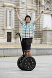 Young happy tourist man wearing safety helmet headgear riding city tour segway driving happy Stock Images