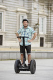 Young happy tourist man wearing safety helmet headgear riding city tour segway driving happy Stock Photos