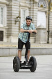 Young happy tourist man wearing safety helmet headgear riding city tour segway driving happy Royalty Free Stock Images