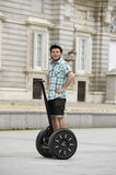 Young happy tourist man wearing safety helmet headgear riding city tour segway driving happy Stock Photography