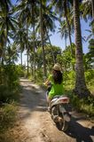 Young happy tourist woman with hat riding scooter motorbike in tropical paradise jungle  with blue sky and palm trees exploring tr. Back view of young happy Royalty Free Stock Photo