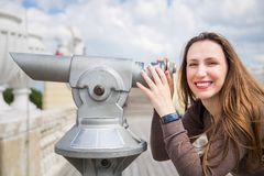 Young tourist girl watching city through telescope stock photography