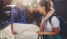 Young happy tourists sightseeing in city. Young happy tourists holding map sightseeing in city Stock Image