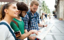 Young happy tourists sightseeing in city. Young happy tourists holding map sightseeing in city Stock Photo