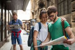 Young happy tourists sightseeing in city. Young happy tourists holding map sightseeing in city Royalty Free Stock Images