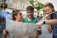 Young happy tourists sightseeing in city. Young happy tourists holding map sightseeing in city Stock Images