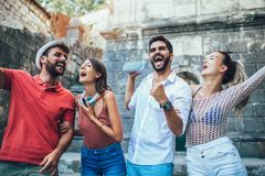 Young happy tourists sightseeing in city. They are having fun listening to music stock photography
