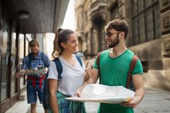 Young happy tourists sightseeing in city. Young happy tourists holding map sightseeing in city Stock Photos