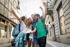 Young happy tourists sightseeing in city. Young happy tourists holding map sightseeing in city Stock Photography