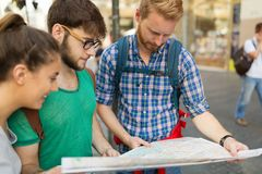 Young happy tourists sightseeing in city. Young happy tourists holding map sightseeing in city Royalty Free Stock Image