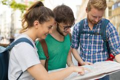 Young happy tourists sightseeing in city. Young happy tourists holding map sightseeing in city Royalty Free Stock Photos