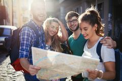 Young happy tourists sightseeing in city. Young happy tourists holding map sightseeing in city Royalty Free Stock Photography