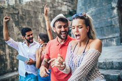Young happy tourists sightseeing in city. They are having fun listening to music stock photo