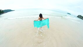 Young girl traveler walking to the sea with veil. Tourism and recreation in Thailand. Charming cute Asian woman travel