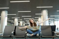 Young happy traveler tourist woman with paper map sit with crossed legs spreading hands as in flight, wait in lobby hall stock photography