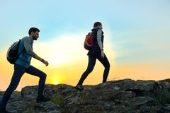 Young Happy Travelers Hiking with Backpacks on the Rocky Trail at Summer Sunset. Family Travel and Adventure Concept. stock images