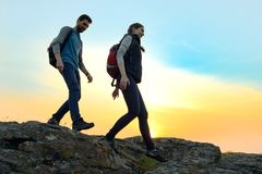 Young Happy Travelers Hiking with Backpacks on the Rocky Trail at Summer Sunset. Family Travel and Adventure Concept. stock photos