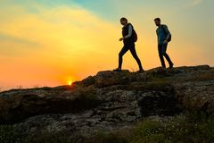 Young Happy Travelers Hiking with Backpacks on the Rocky Trail at Summer Sunset. Family Travel and Adventure Concept. royalty free stock images