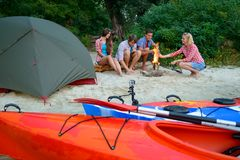 Young Happy Travelers Resting at Evening with Fire on the Sand Beach near Kayaks and Tent. Stock Photography