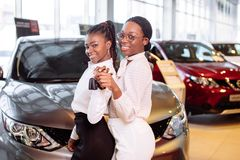 Two african american woman near car with keys in hand - concept of buying car royalty free stock images