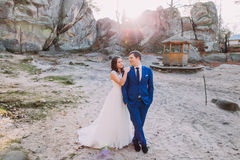 Young happy white dressed bride leaning on shoulder of her handsome confident groom in blue suit Royalty Free Stock Images