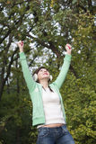 Young happy winner girl enjoying life and the fresh air in green. Portrait of happy young girl raised hands to the sky in the forest Stock Image