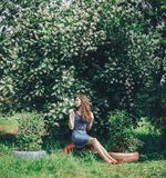 Pappy woman in an apple orchard in the spring flowers white. Young happy woman in an apple orchard in the spring flowers white Royalty Free Stock Photo