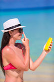 Young happy woman applying suntan lotion on her. Young woman apply cream on her nose at beach Stock Images