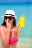 Young happy woman applying suntan lotion on her. Young woman apply cream on her nose at beach Stock Image