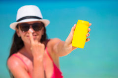 Young happy woman applying suntan lotion on her. Young woman apply cream on her nose at beach Stock Photography