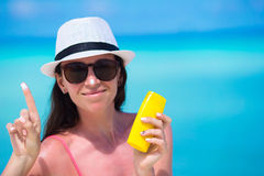 Young happy woman applying suntan lotion on her. Young woman apply cream on her nose at beach Stock Photo