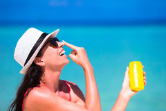 Young happy woman applying suntan lotion on her. Young woman apply cream on her nose at beach Stock Photos