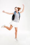 Young happy woman with backpack jumping and celebrating success Stock Images