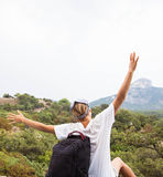 Young happy woman with backpack relaxing on a rock Royalty Free Stock Photography