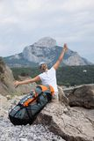 Young happy woman with backpack relaxing on a rock Royalty Free Stock Photo