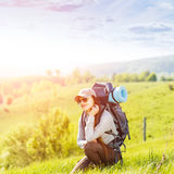 Young happy woman with backpack resting on hill Royalty Free Stock Photo