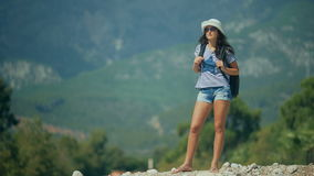 Young happy woman with backpack standing in the mountains and looking to a valley below.  stock video